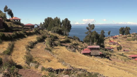 Peru-Taquile-terraced-hill-and-distant-stone-arch-near-lake-25