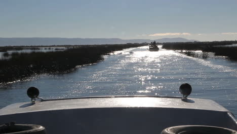 Peru-Lake-Titicaca-boat-trails-another-boat-through-sparkling-water