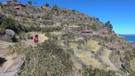 Peru-Taquile-hillside-woman-approaches-with-heavy-load