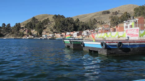 Peru-Lake-Titicaca-flags-and-dock-recede-as-boat-leaves