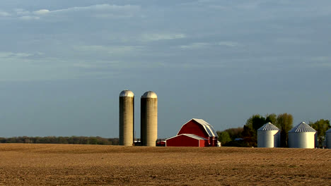Zooms-out-from-a-red-barn-and-silos-to-a-country-road-