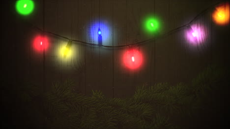 Animated-closeup-colorful-garland-and-Christmas-green-tree-branches-on-wood-1