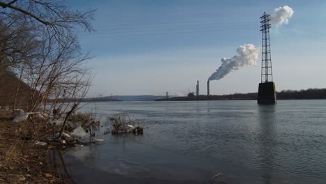 Smoke-rises-from-a-distant-power-plant-along-a-river