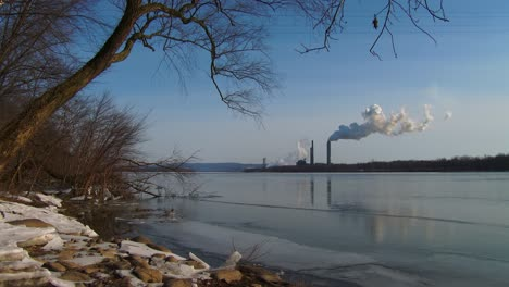 Smoke-rises-from-a-distant-power-plant-along-a-river-2