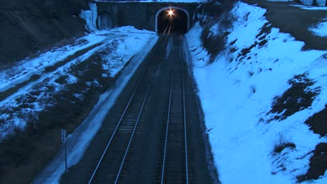 High-angle-over-a-freight-train-going-through-a-tunnel-at-night-in-the-winter