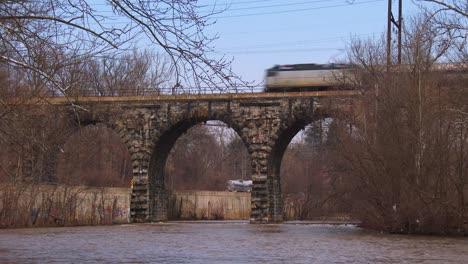 Un-Tren-De-Pasajeros-Pasa-Por-Un-Viejo-Puente-De-Piedra
