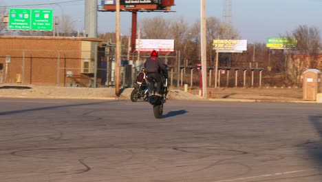 A-rider-performs-stunts-on-a-motorcycle-in-a-parking-lot