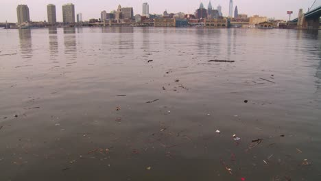 Tilt-up-to-ugly-brown-pollution-in-a-river-with-Philadelphia-Pennsylvania-background