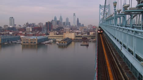 A-commuter-train-crosses-the-Ben-Franklin-Bridge-with-Philadelphia-PA-in-background