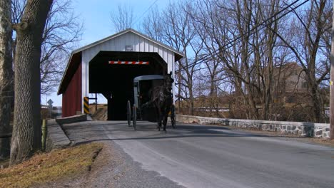 An-Amish-horse-cart-travels-through-a-covered-bridge-along-a-road-in-rural-Pennsylvania