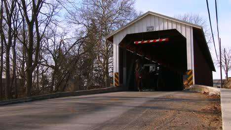An-Amish-horse-cart-travels-through-a-covered-bridge-along-a-road-in-rural-Pennsylvania-3