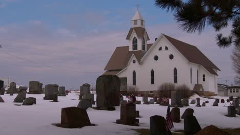 A-white-church-with-snow-and-graves-in-foreground