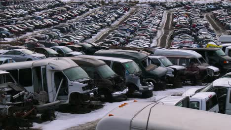 Cars-sit-in-rows-in-a-junkyard-in-the-snow