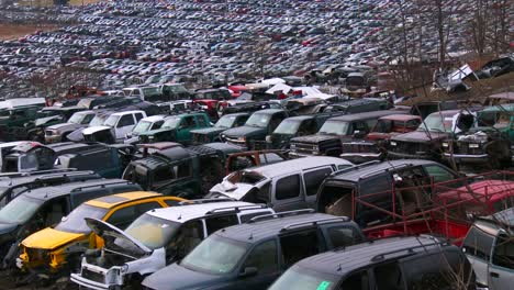 Cars-sit-in-rows-in-a-vast-junkyard-in-the-snow