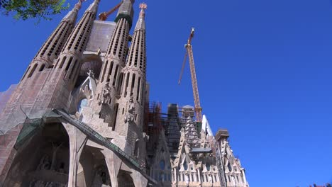 Low-angle-pan-across-the-Sagrada-Familia-cathedral-by-Gaudi-in-Barcelona-Spain