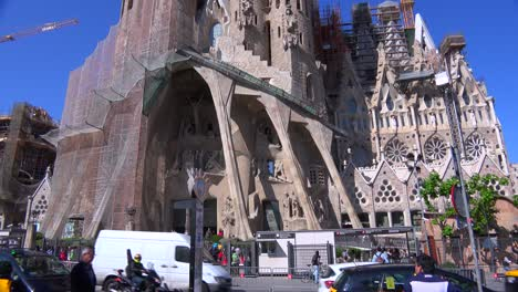 Traffic-passes-at-the-base-of-of-the-Sagrada-Familia-cathedral-by-Gaudi-in-Barcelona-Spain