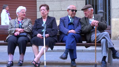 Old-couples-sit-on-a-park-bench-and-gossip-in-Spain