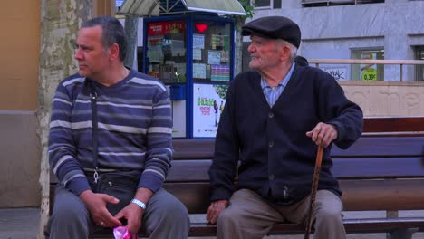 Two-men-sit-on-a-park-bench-in-Spain