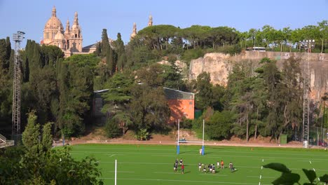 A-football-team-conducts-a-practice-on-a-field-with-Barcelona-National-palace-background