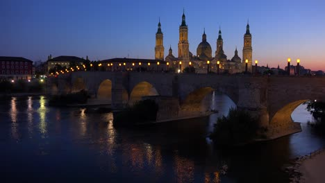 A-classic-and-beautiful-stone-bridge-in-Zaragoza-Spain-at-dusk-with-Catholic-cathedral-background