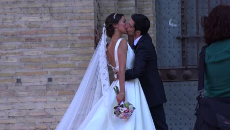 A-bride-and-groom-kiss-on-a-public-street-while-a-photographer-snaps-pictures