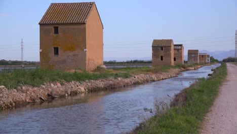 Unusual-square-adobe-huts-along-an-irrigation-canal-near-Albufera-Spain