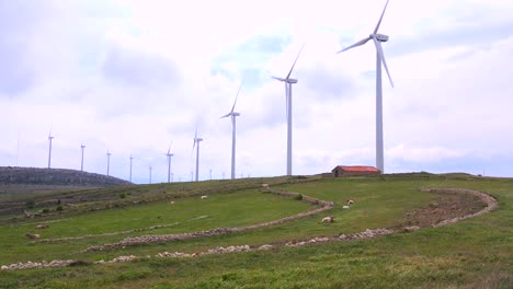 Wide-shot-of-windmills-generating-electricity-near-traditional-villages-in-Spain