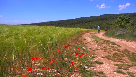 A-young-girl-walks-along-a-dirt-road-near-a-field-of-wildflowers