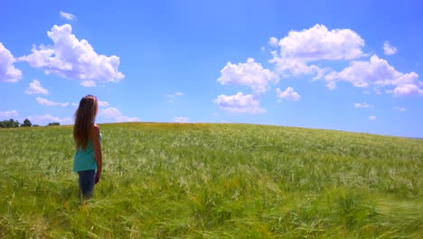 A-pretty-young-girl-stands-in-a-field-with-her-hair-blowing