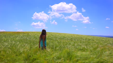 A-pretty-young-girl-walks-in-a-field-with-her-hair-blowing