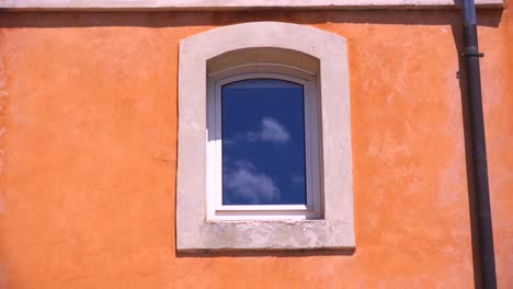 Sky-and-clouds-reflected-in-a-pastel-building-in-Provence-France