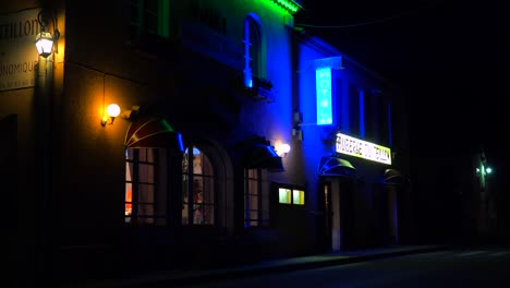 A-small-French-hotel-at-night-with-neon-sign-flashing