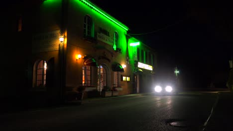 A-car-passes-a-small-French-hotel-at-night-with-neon-sign-flashing