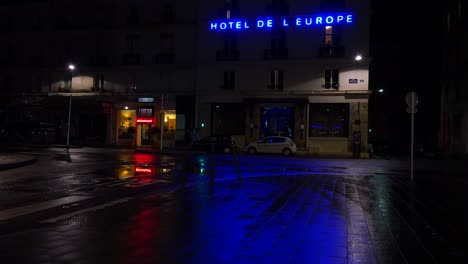 A-hotel-sign-is-reflected-in-rainy-streets-of-Paris-or-France