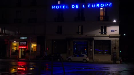A-hotel-sign-is-reflected-in-rainy-streets-of-Paris-or-France-with-a-light-on-upstairs