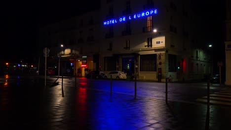 A-hotel-sign-is-reflected-in-rainy-streets-of-Paris-or-France-with-a-light-on-upstairs-1