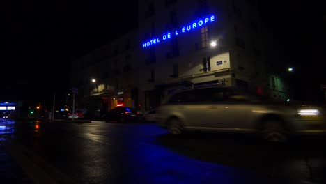 A-hotel-sign-is-reflected-in-rainy-streets-of-Paris-or-France-with-a-light-on-upstairs-2