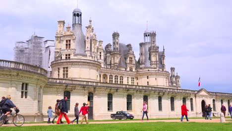 Bicyclists-ride-in-front-of-the-beautiful-chateau-of-Chambord-in-the-Loire-Valley-in-France