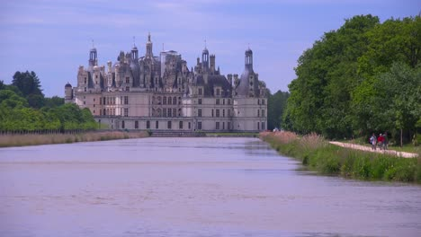 Long-view-down-a-canal-to-the-beautiful-chateau-of-Chambord-in-the-Loire-Valley-in-France-2