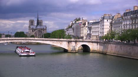 A-riverboat-travels-under-bridges-near-the-Notre-Dame-cathedral-in-Paris