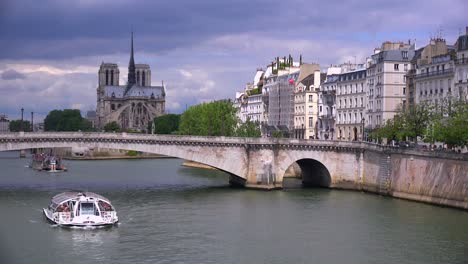 A-riverboat-travels-under-bridges-near-the-Notre-Dame-cathedral-in-Paris-1