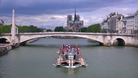 A-riverboat-travels-under-bridges-near-the-Notre-Dame-cathedral-in-Paris-2