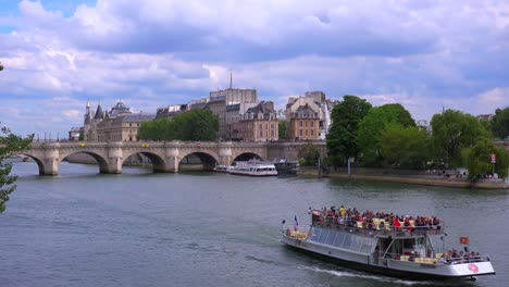 A-riverboat-travels-under-bridges-near-the-Notre-Dame-cathedral-in-Paris-3