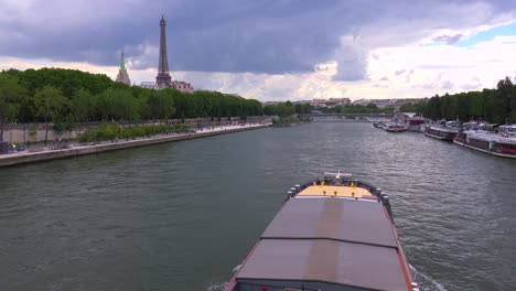 A-bateaux-mouche-riverboat-passes-under-the-camera-near-the-Eiffel-Tower