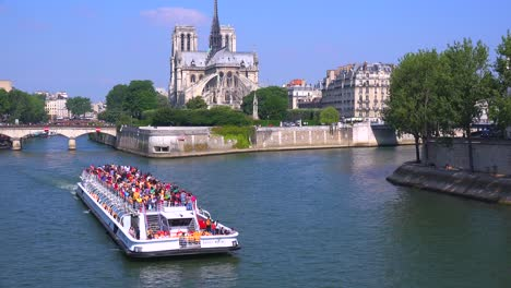 A-riverboat-travels-on-the-Seine-near-the-Notre-Dame-cathedral-in-Paris