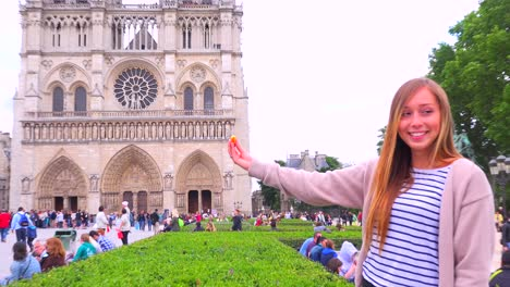 Birds-feed-from-a-young-girls-hand-in-front-of-Notre-Dame-cathedral-in-paris