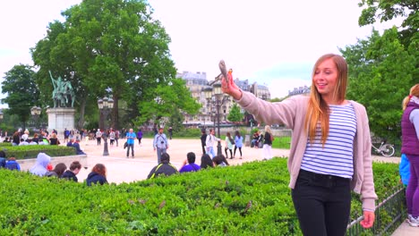Birds-feed-from-a-young-girls-hand-in-front-of-Notre-Dame-cathedral-in-paris-1