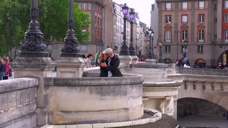 A-man-and-woman-kiss-on-a-Paris-bridge