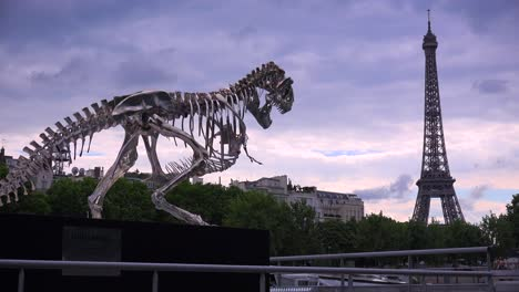 A-dinosaur-sculpture-stands-with-the-Eiffel-Tower-background