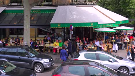 A-classic-Paris-outdoor-cafe-with-many-patrons-and-waiters-serving